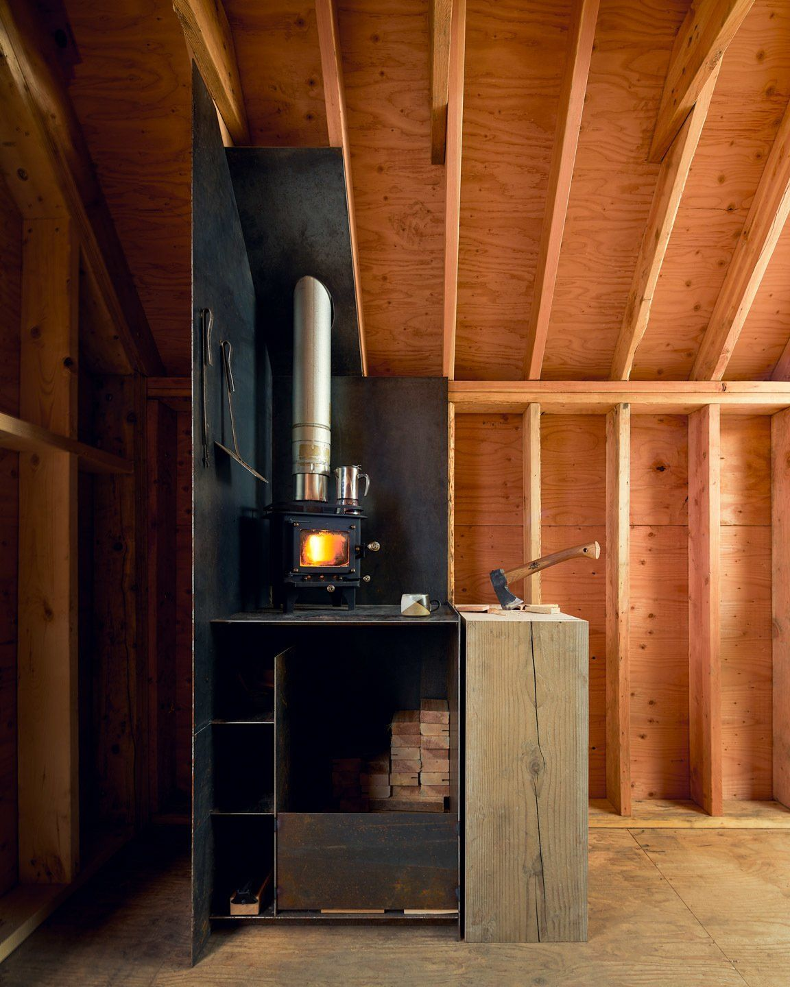 Inside, the cabin looks very cozy, especially with this wood-burning stove in the corner