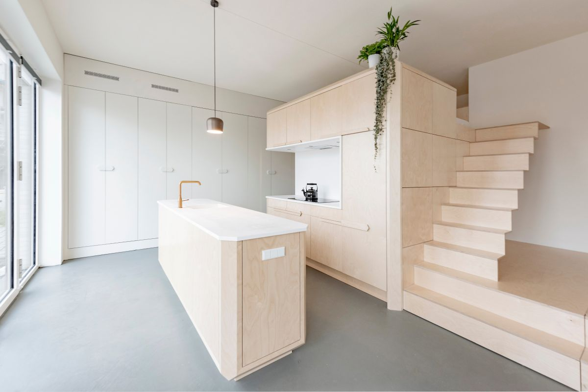 The kitchen island matches the storage unit and loft bed area, maintaining a harmonious aesthetic