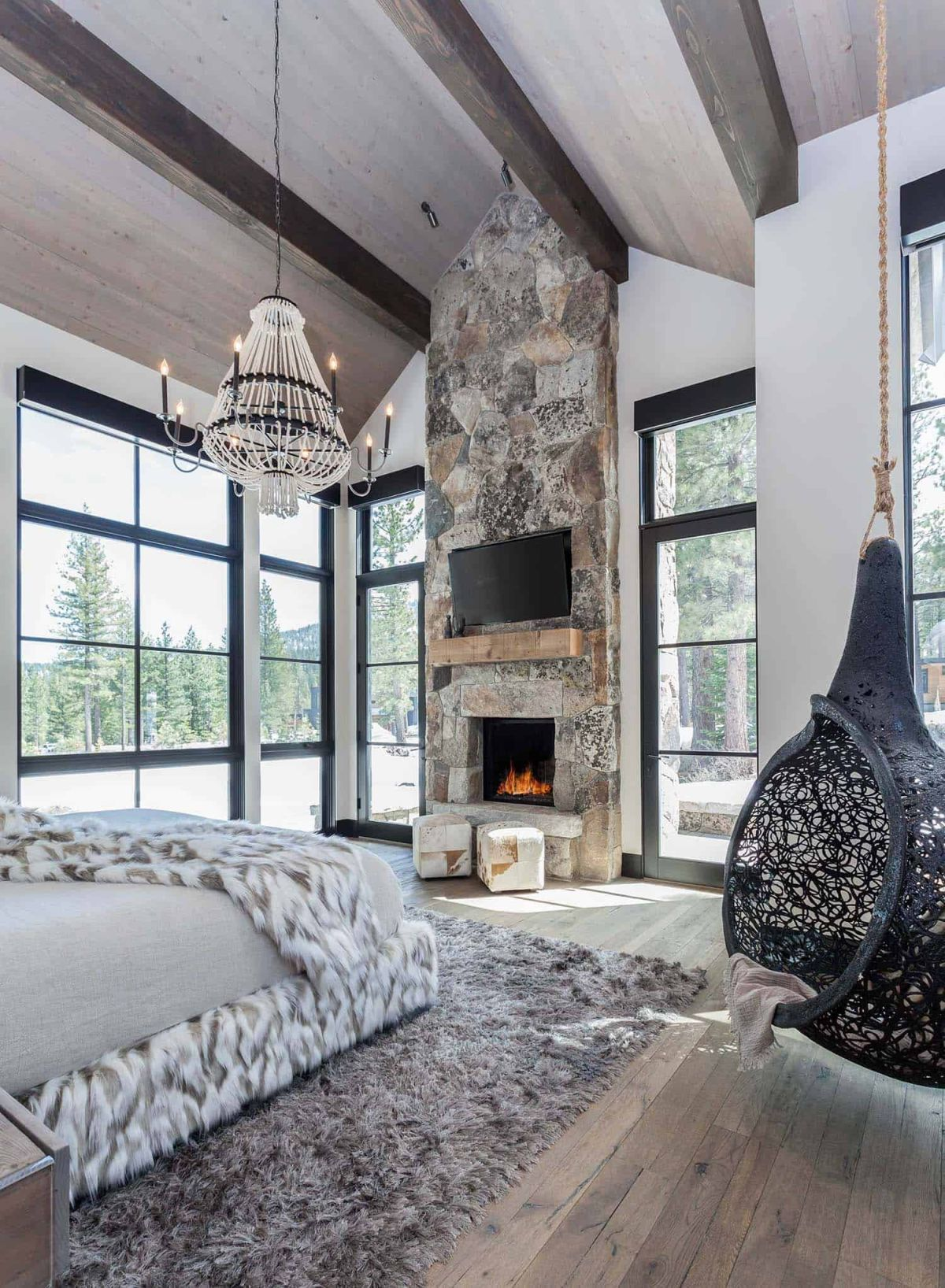 The master bedroom has its own stone fireplace which emphasizes the height of the space in a very nice way
