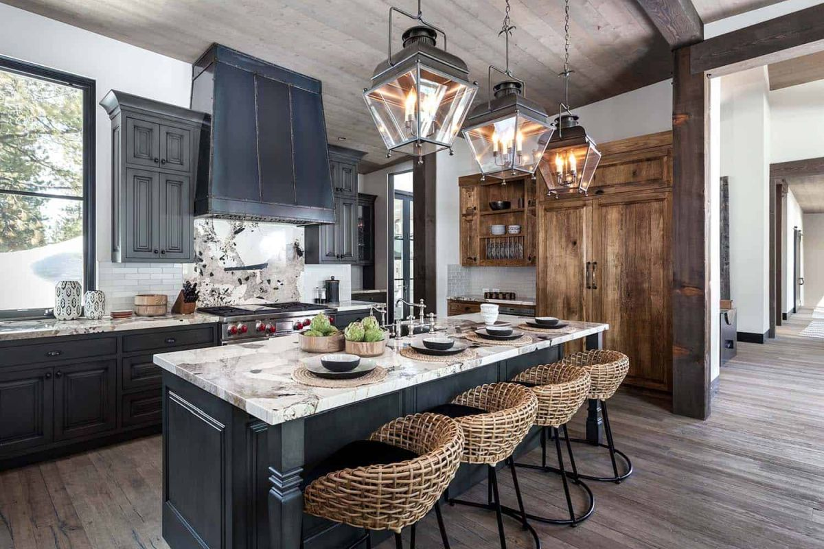 The kitchen island is complemented by four comfy basket chairs and rustic lantern pendant lamps