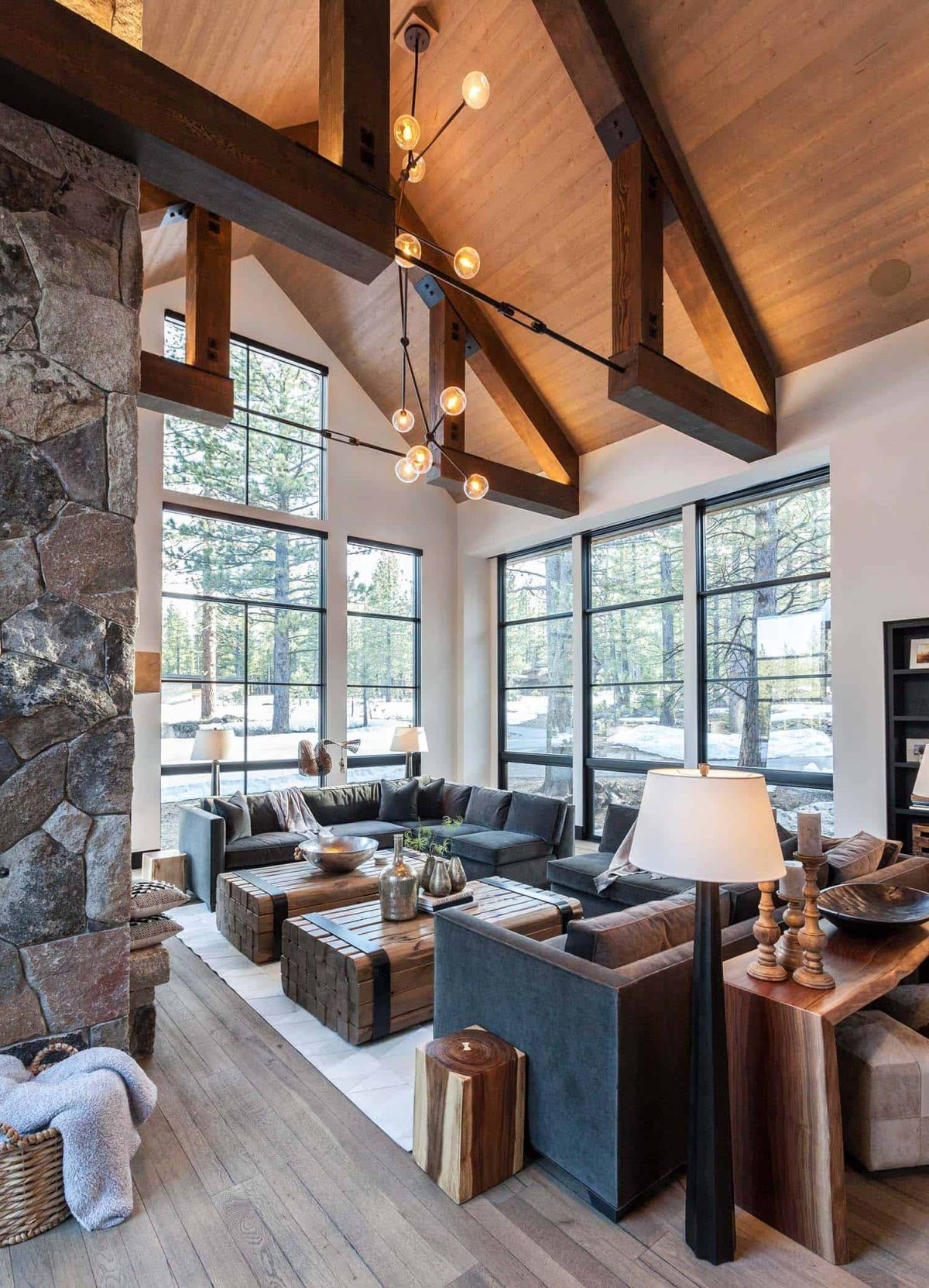The seating area has comfortable, gray sofas, two wooden coffee tables and stylish lighting fixtures
