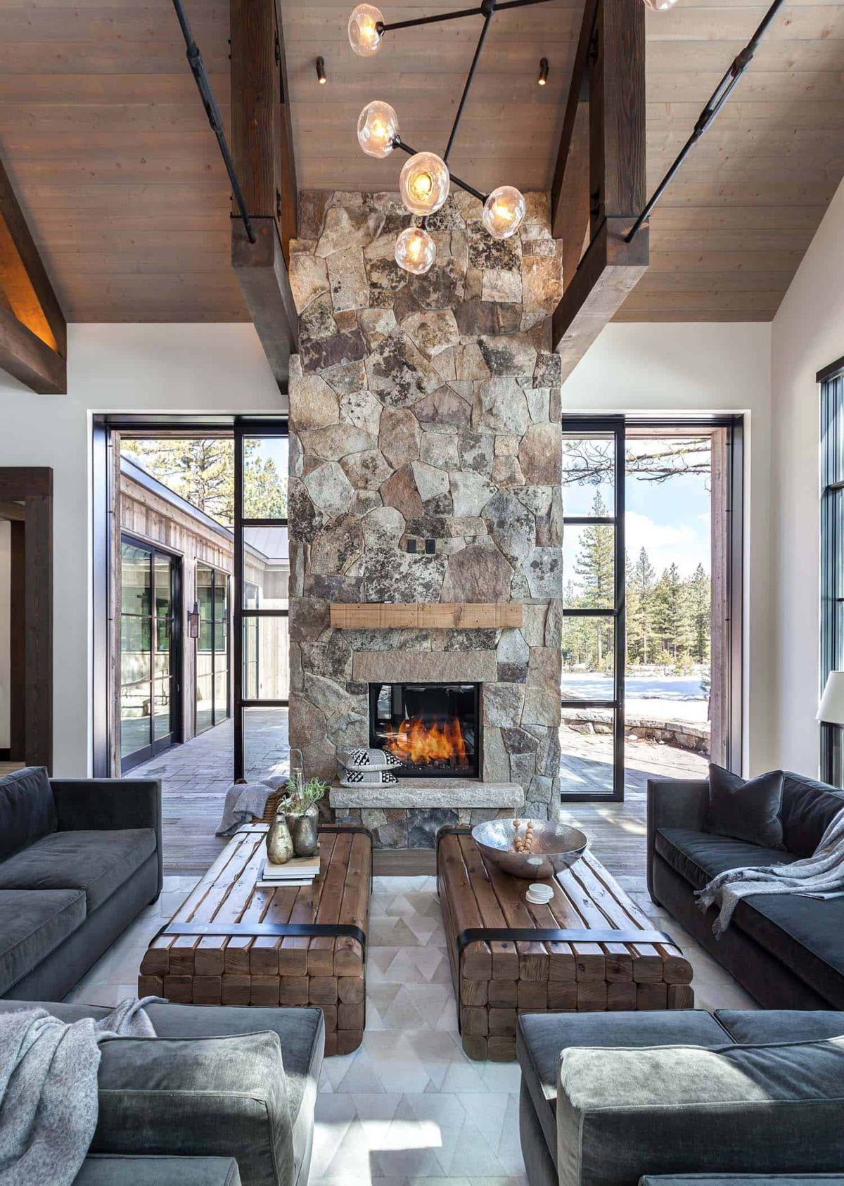The floor-to-ceiling stone fireplace in the living room has sliding doors on either side which disappear inside it when open