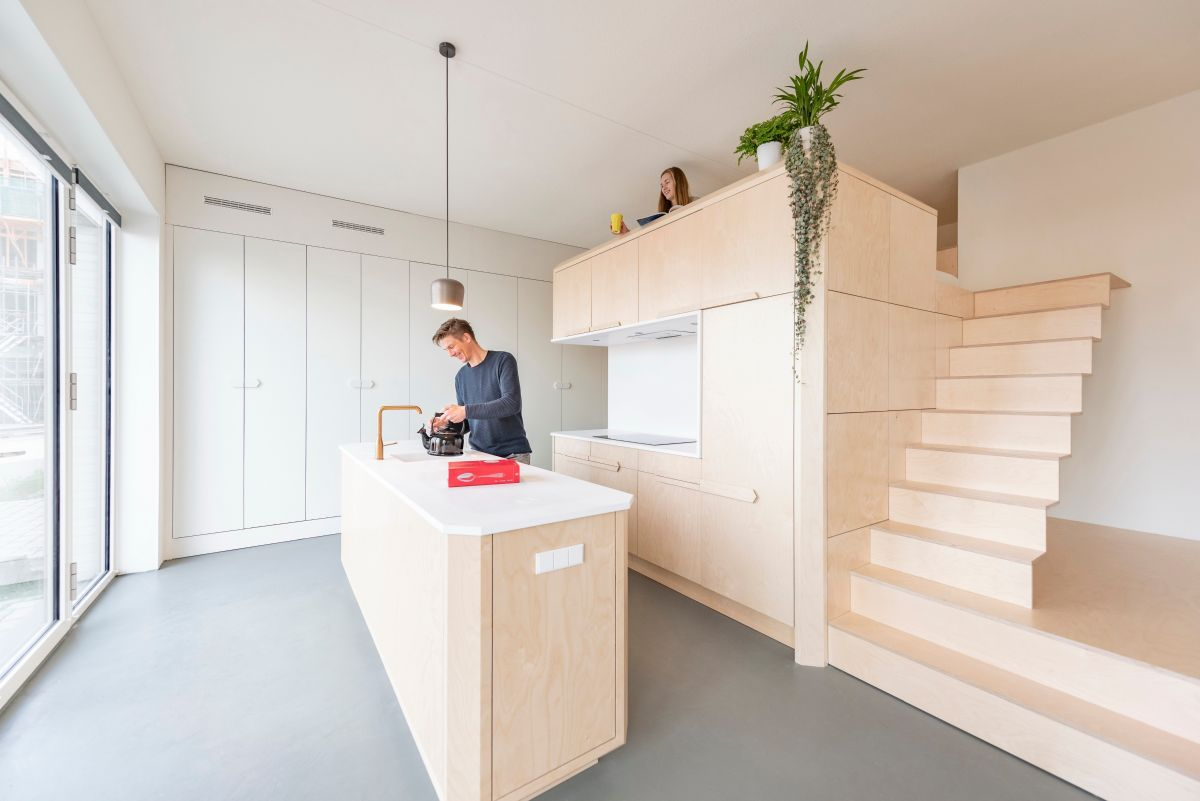 The kitchen and loft bed are merged into a single large unit built out of birch wood