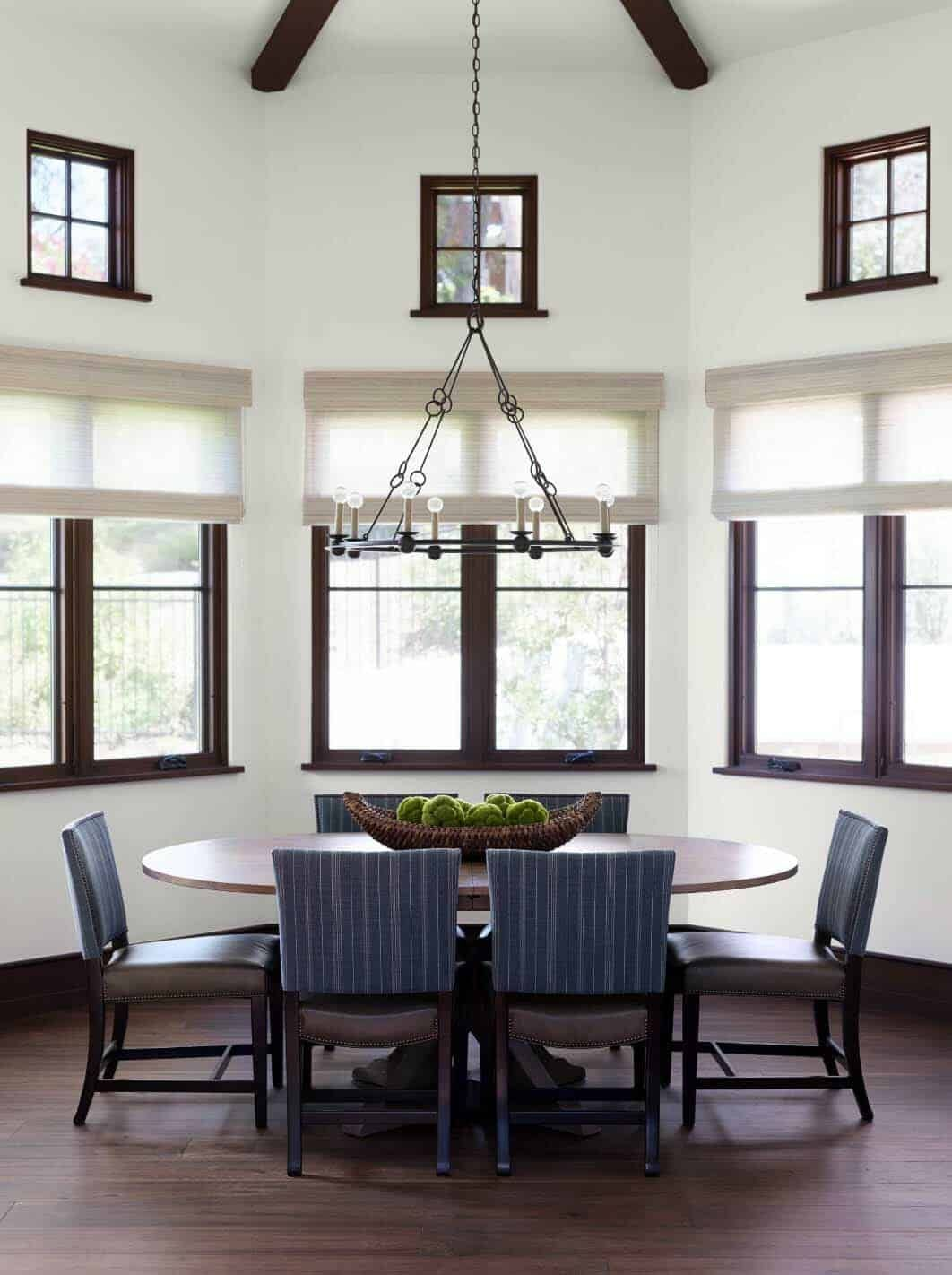 The dining room is framed by windows and has a circular wooden table with leather chairs all around