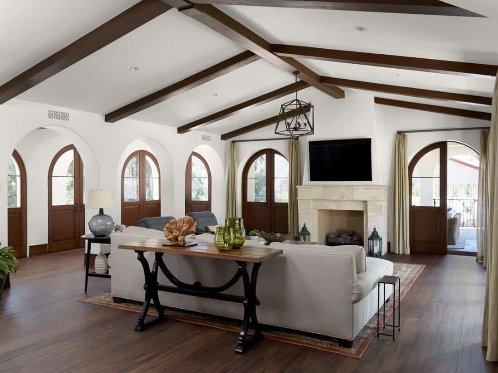 The living room has white walls, a white ceiling and a beautiful dark wood floor