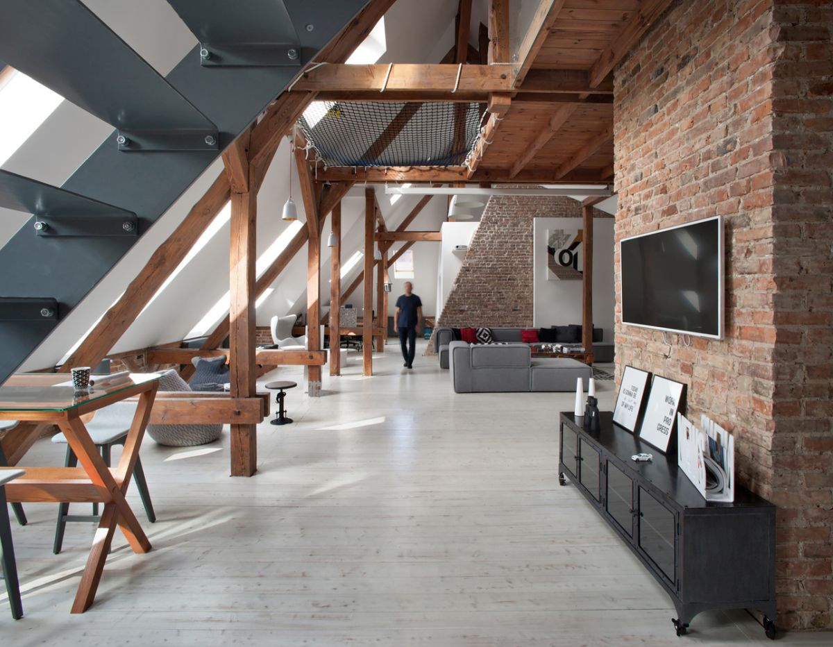 The combination of brick walls, steel stairs and exposed beams gives the apartment a strong industrial vibe