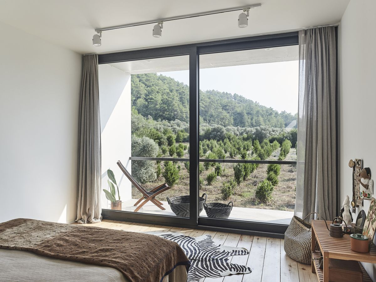 The bedroom has its own tiny balcony and full-height windows that bring the outdoors in