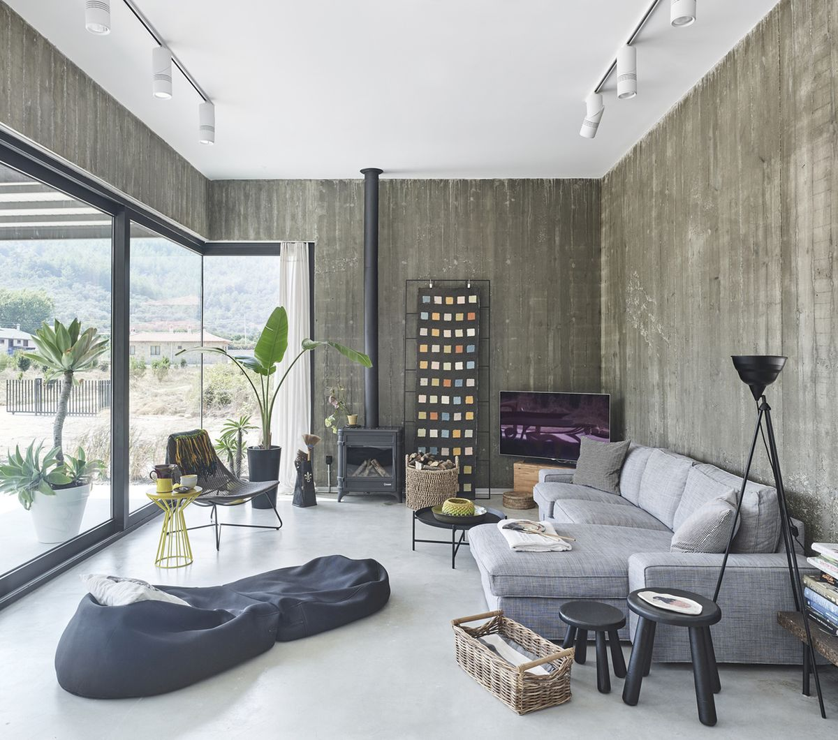 In the living room there's a comfy sectional sofa complemented by various accent tables, poufs and chairs
