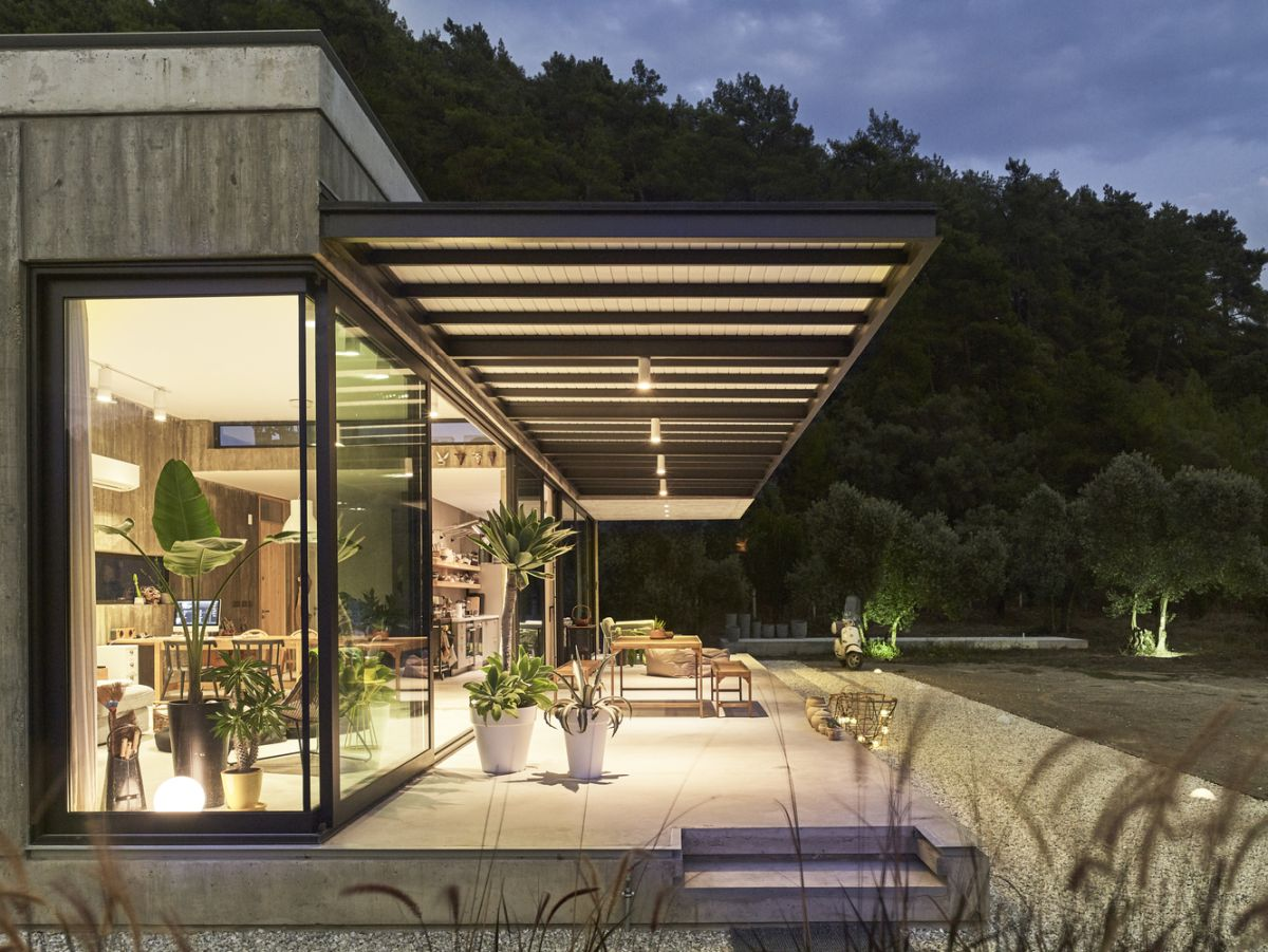 The living areas extend outside onto a sleek deck with majestic views