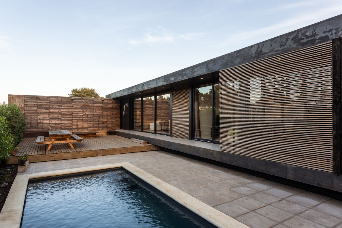 An inner courtyard is sheltered by a wall wood-covered wall and by vegetation
