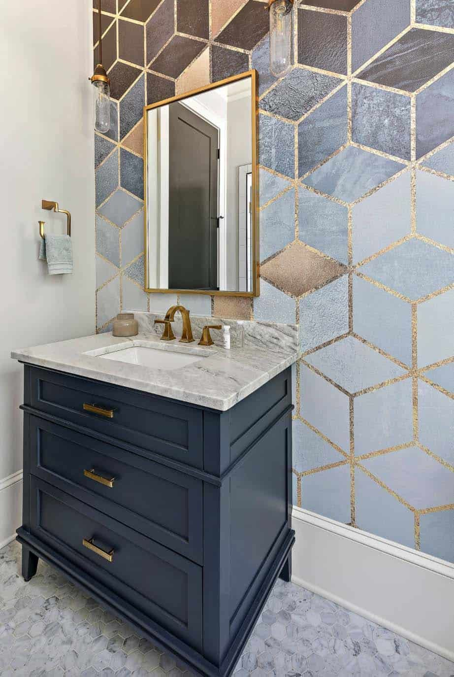 This bathroom has an eye-catching accent wall and a stylish antique brass mirror