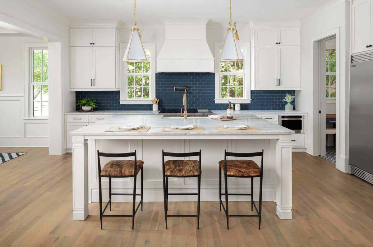 The kitchen has a large island, white walls, white furniture and a navy blue backsplash
