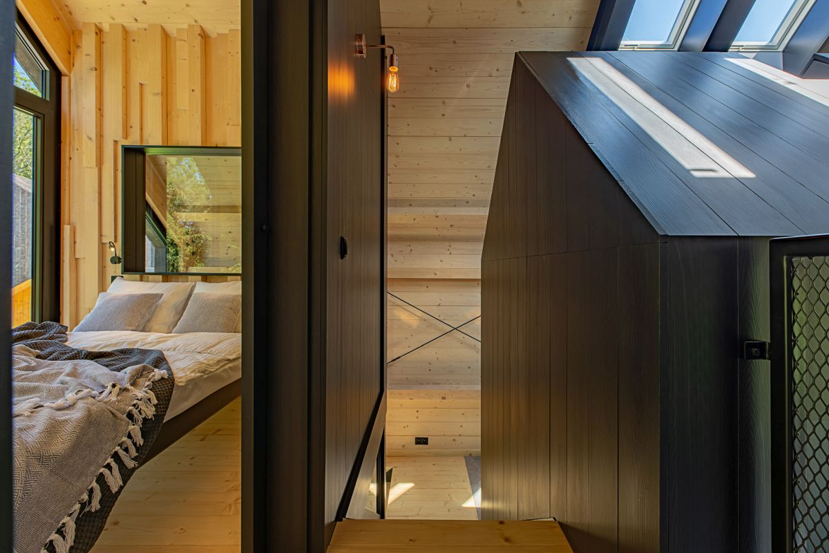 One of the bedrooms is situated upstairs next to the staircase and has a view of the rear deck and the forest beyond