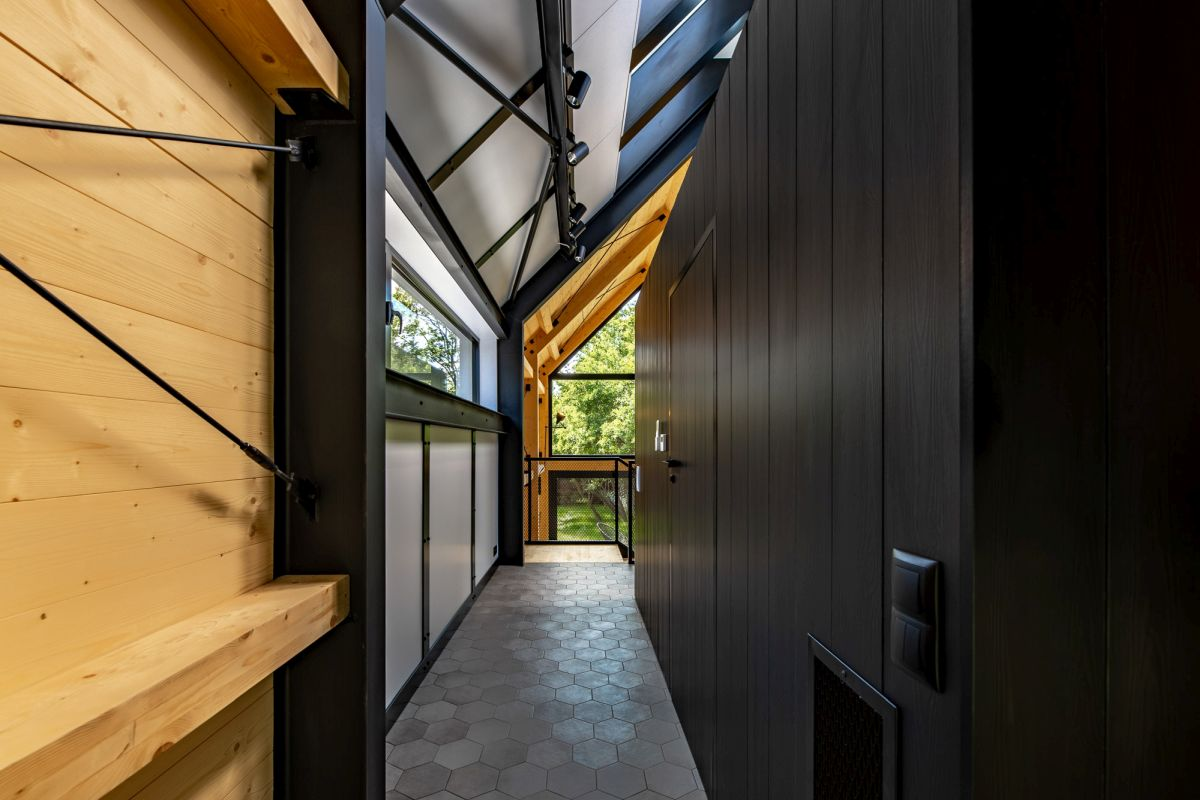 The interior design is defined by extensive black surfaces complemented by natural wood and large windows