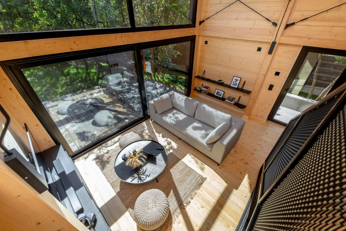Large sliding doors open the living room towards a deck, inviting guests to celebrate nature