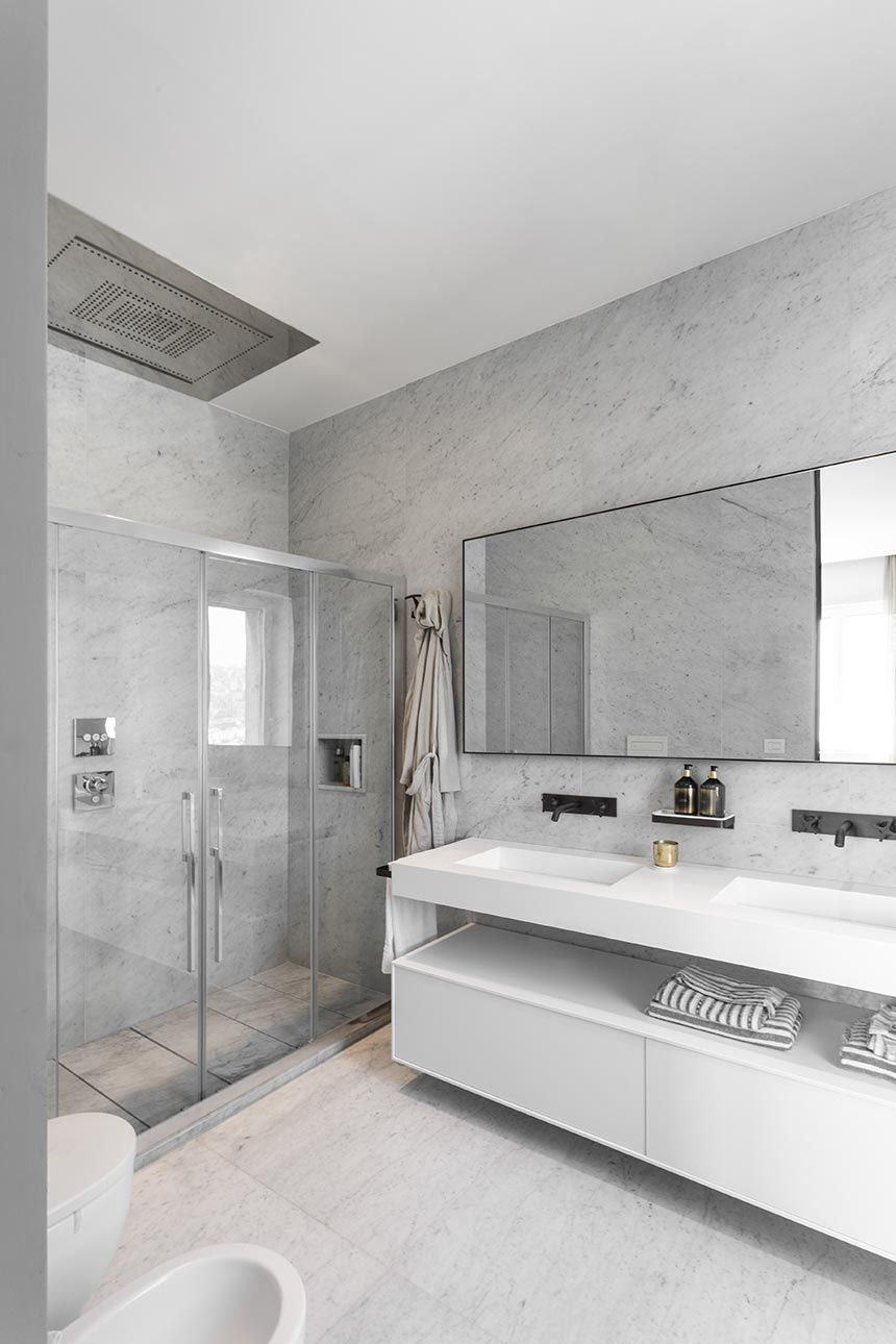 The en-suite bathroom is almost entirely covered in white Carrara marble and looks super bright and airy