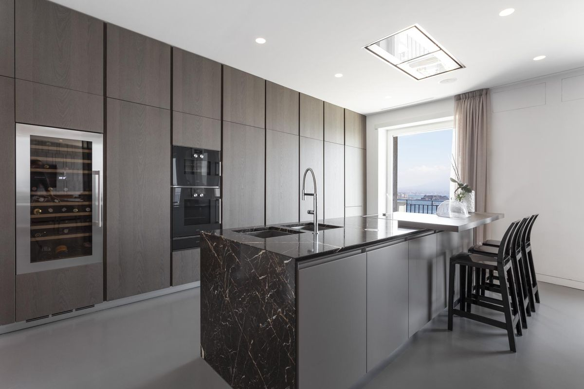 The kitchen is spacious, with a custom storage wall, built-in appliances and an elegant island