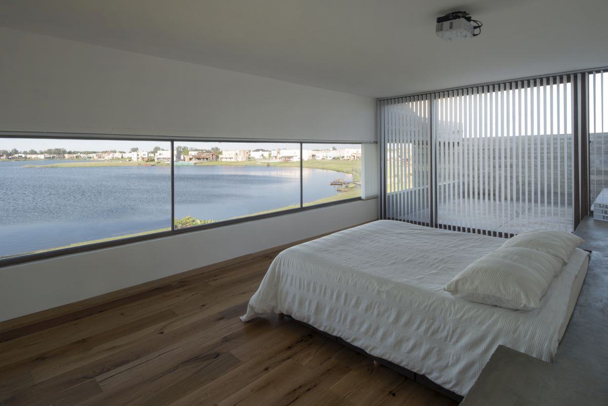 The master bedroom features a set of wide, horizontally narrow windows which overlook the lagoon