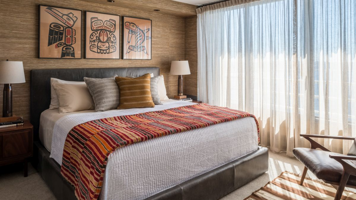 The bedroom features delicate curtains, lots of wood and a variety of textured details
