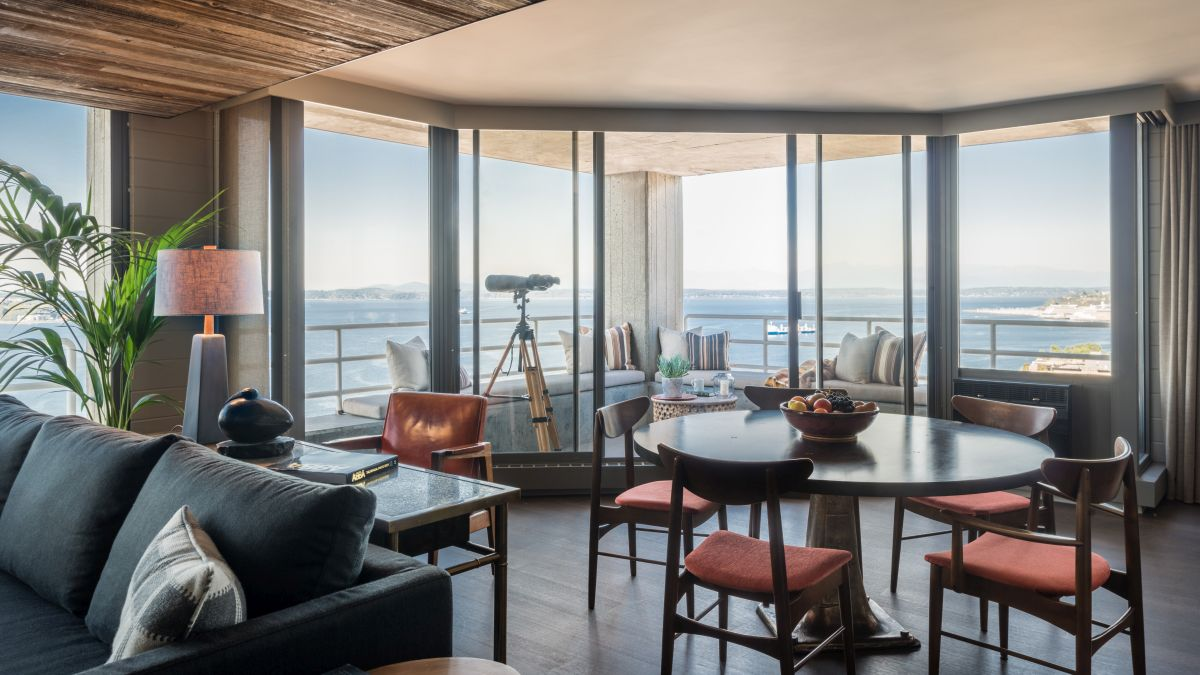 The dining area is framed by a curved balcony with a panoramic coastal view