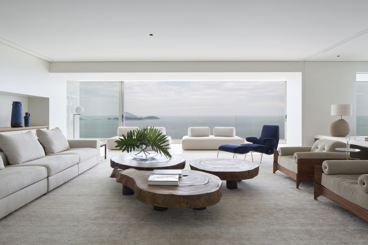 The living room featured three live edge wood tables at the center, surrounded by sofas and armchairs
