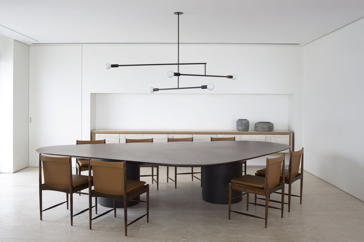 The dining table is very large and surrounded by eight elegant and comfortable chairs