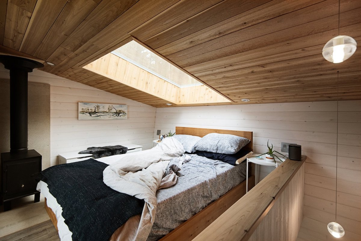 The lofted bedroom is small and cozy and has a skylight just above the bed
