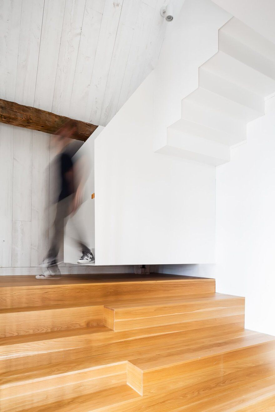 The wooden stairs don't actually go all the way up but are paired with a second white staircase