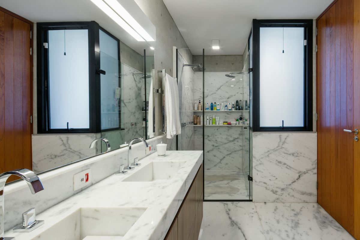 White marble and a huge mirror give the bathroom a bright and timeless feel