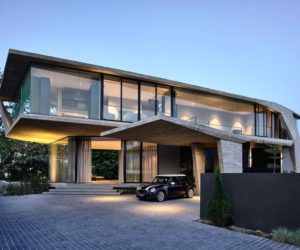 A Stylish Glass And Concrete House Shielded By Lush Greenery