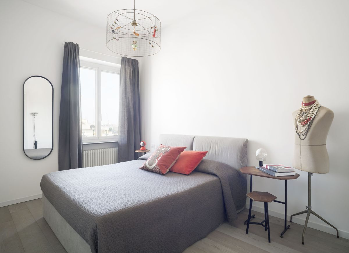 This bedroom is simple and has a delicate and feminine vibe, featuring soft greys and red accents