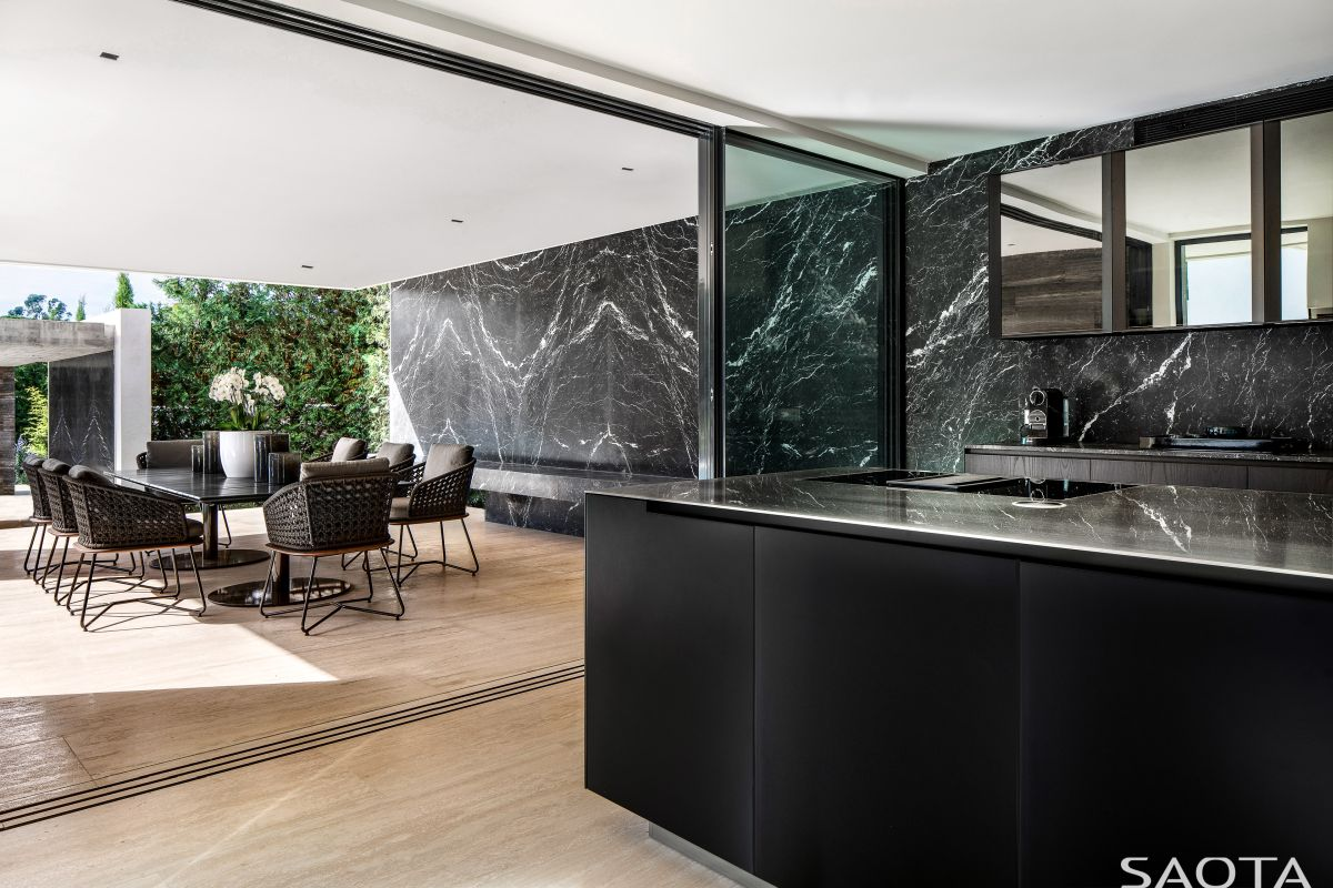 Black marble surfaces add elegance to the interior design and establish a harmonious connection with the wooden flooring