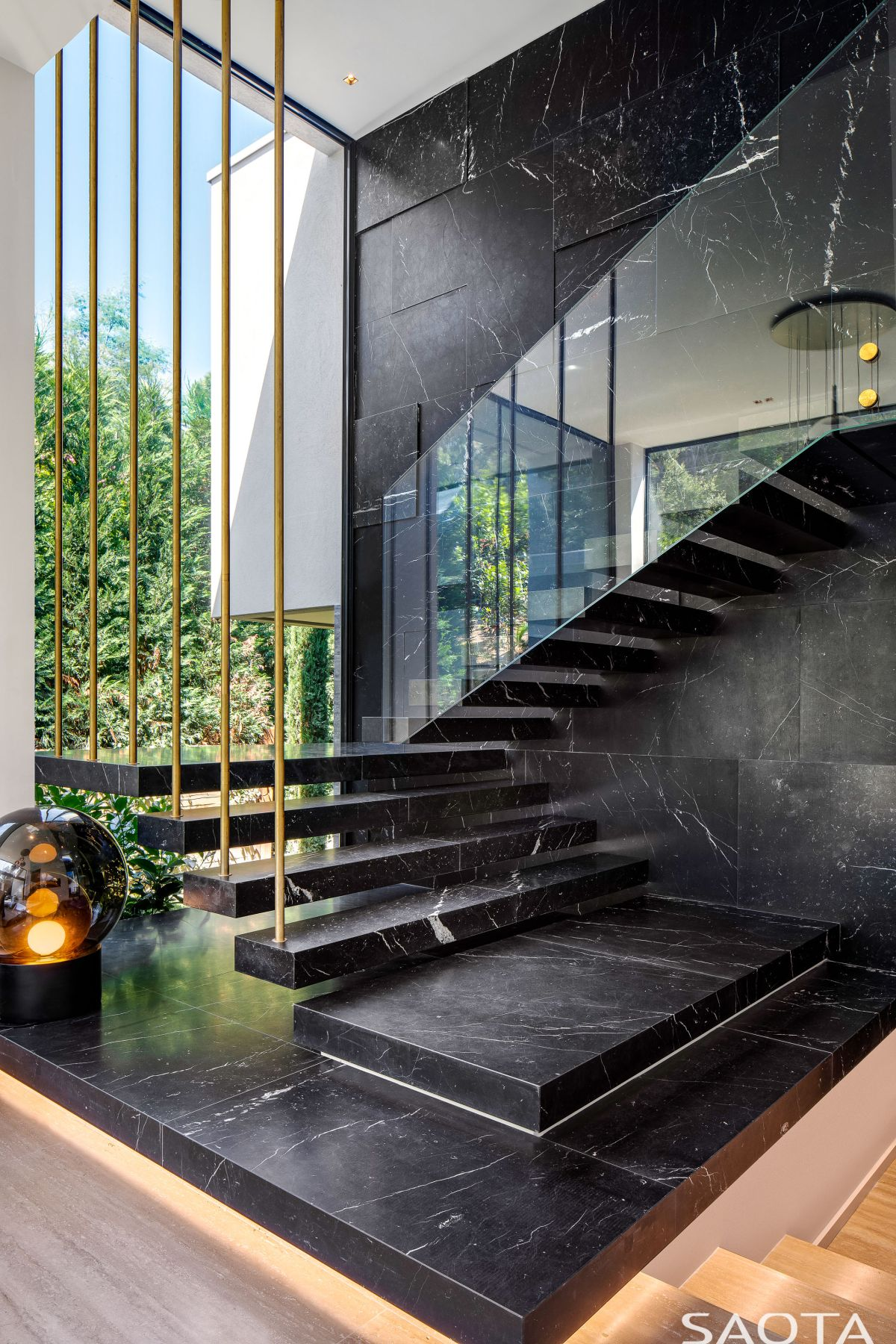 A staircase connects the master bedroom suite to a private lounge area with a double height ceiling