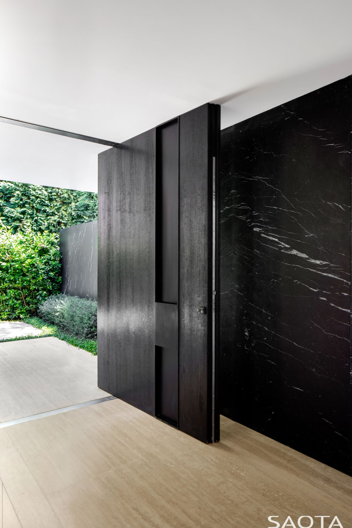 The main entrance is defined by a large and solid pivot door which contrasts with the white walls around it