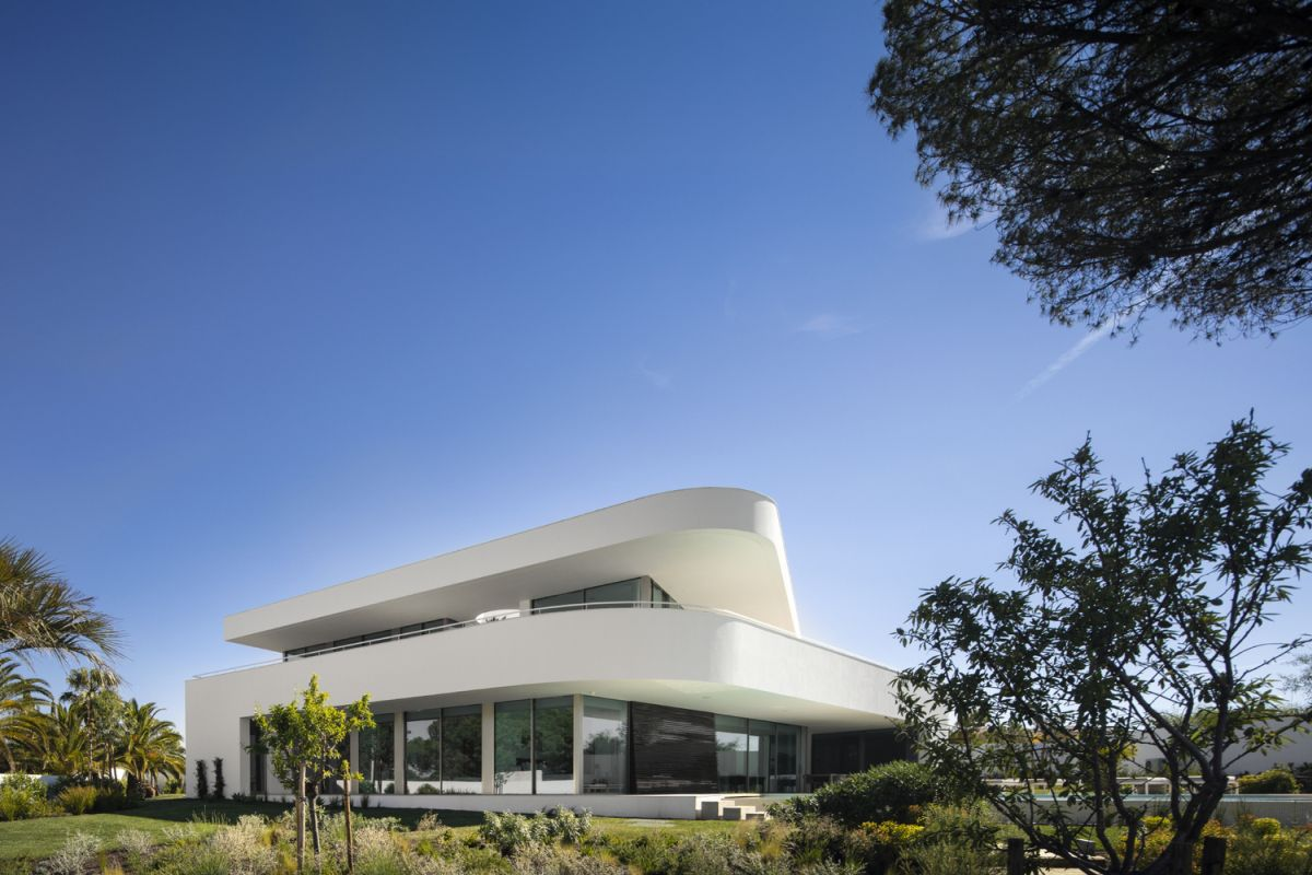 The curved edges and clean lines of the houses reference the surrounding landscape and the ocean