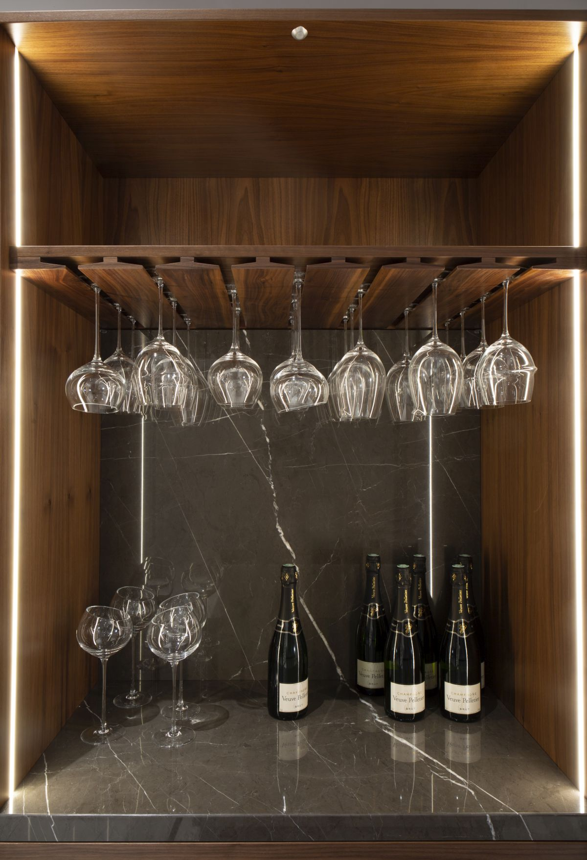 An elegant glass holding rack is seamlessly integrated into the bar unit, adding function without complicating the aesthetic