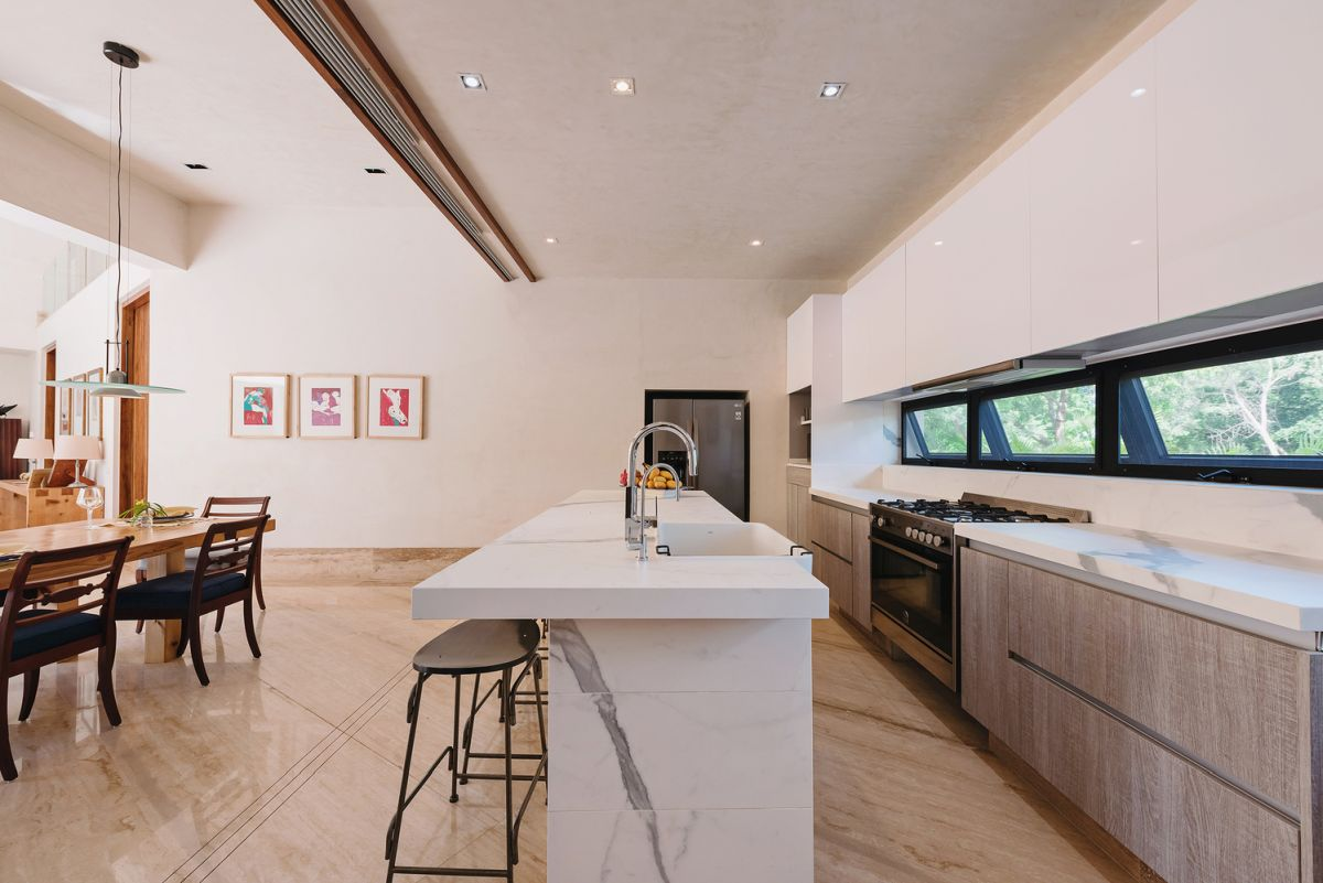 The white marble kitchen island contrasts with the rest of the decor and adds an elegant touch to the space