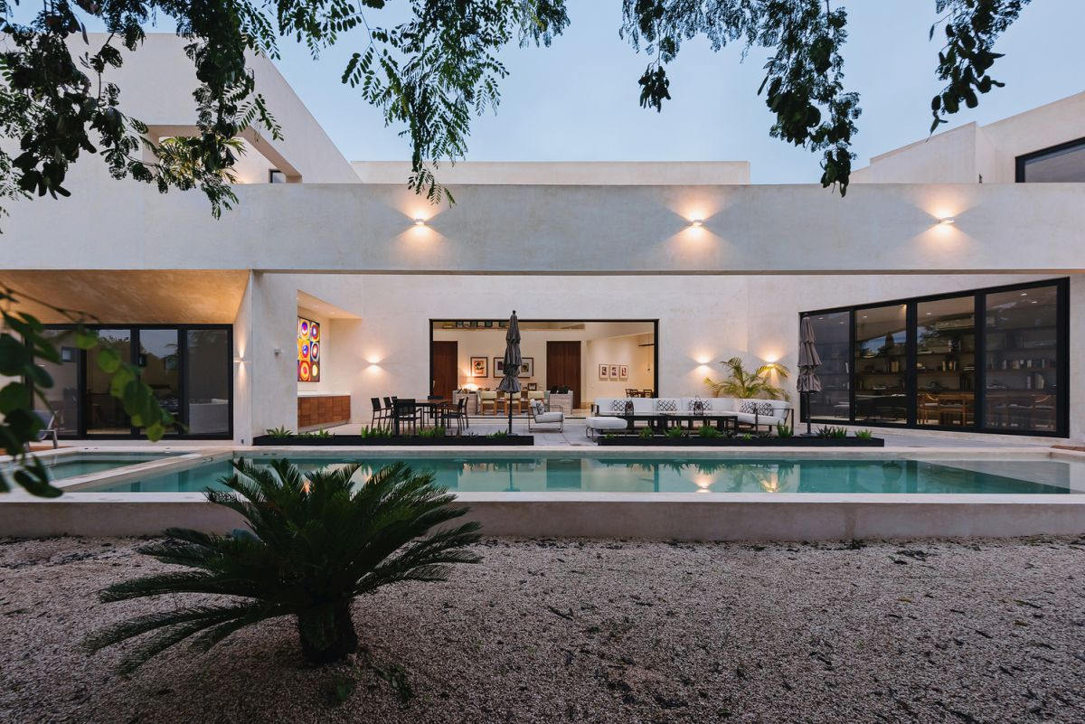 the indoor living areas seamlessly open towards a terrace which is turn connects to the swimming pool