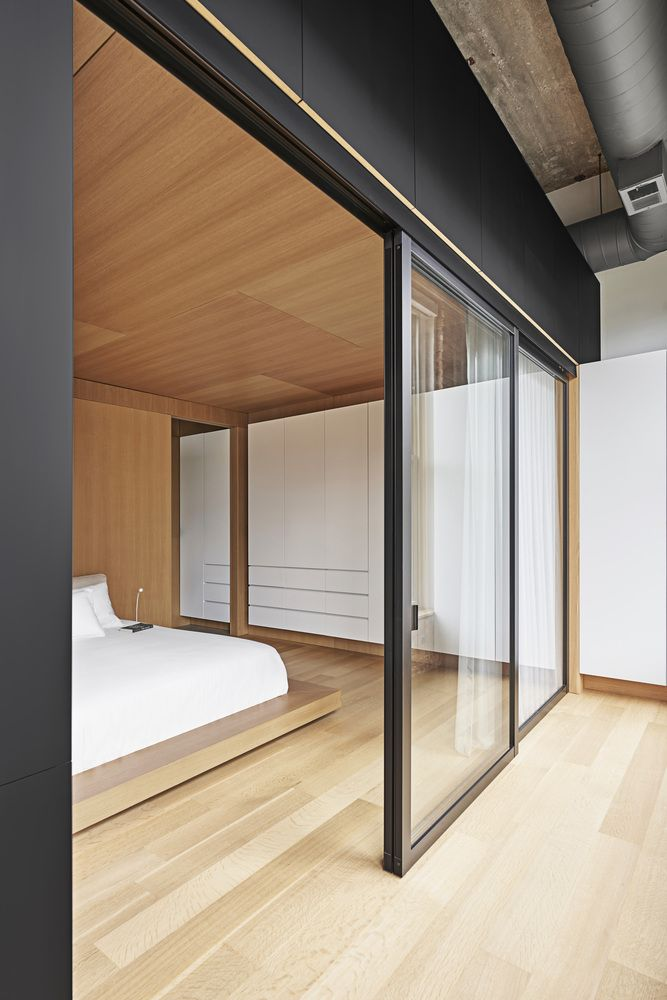 Glass partitions allow light to enter the bedroom and prevent it from feeling small and cluttered