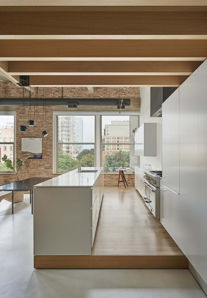 The kitchen is seamlessly integrated into the open plan volume but stands out and has a slightly raised floor