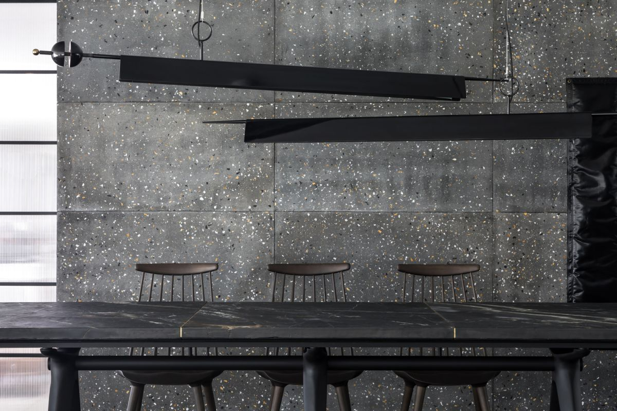 The dining area is lit by two minimalis and linear pendant lights with a black finish