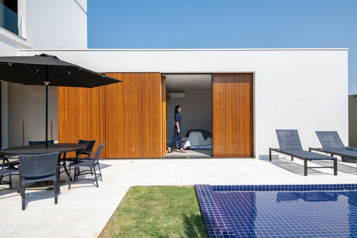 Sliding wooden dividers filter the sunlight and allow the indoor spaces to open up to the garden