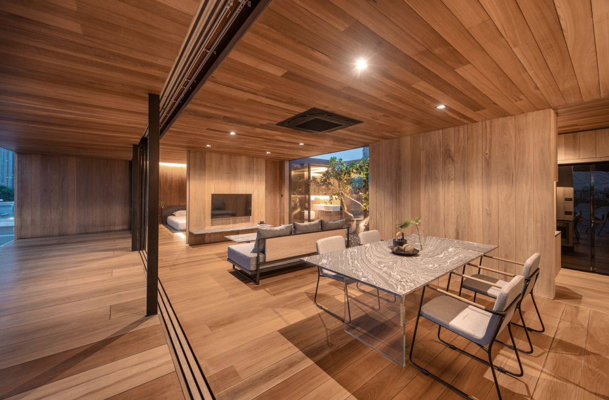 Wood planks cover up the entire house inside and out and contrast with the concrete surfaces that surround it