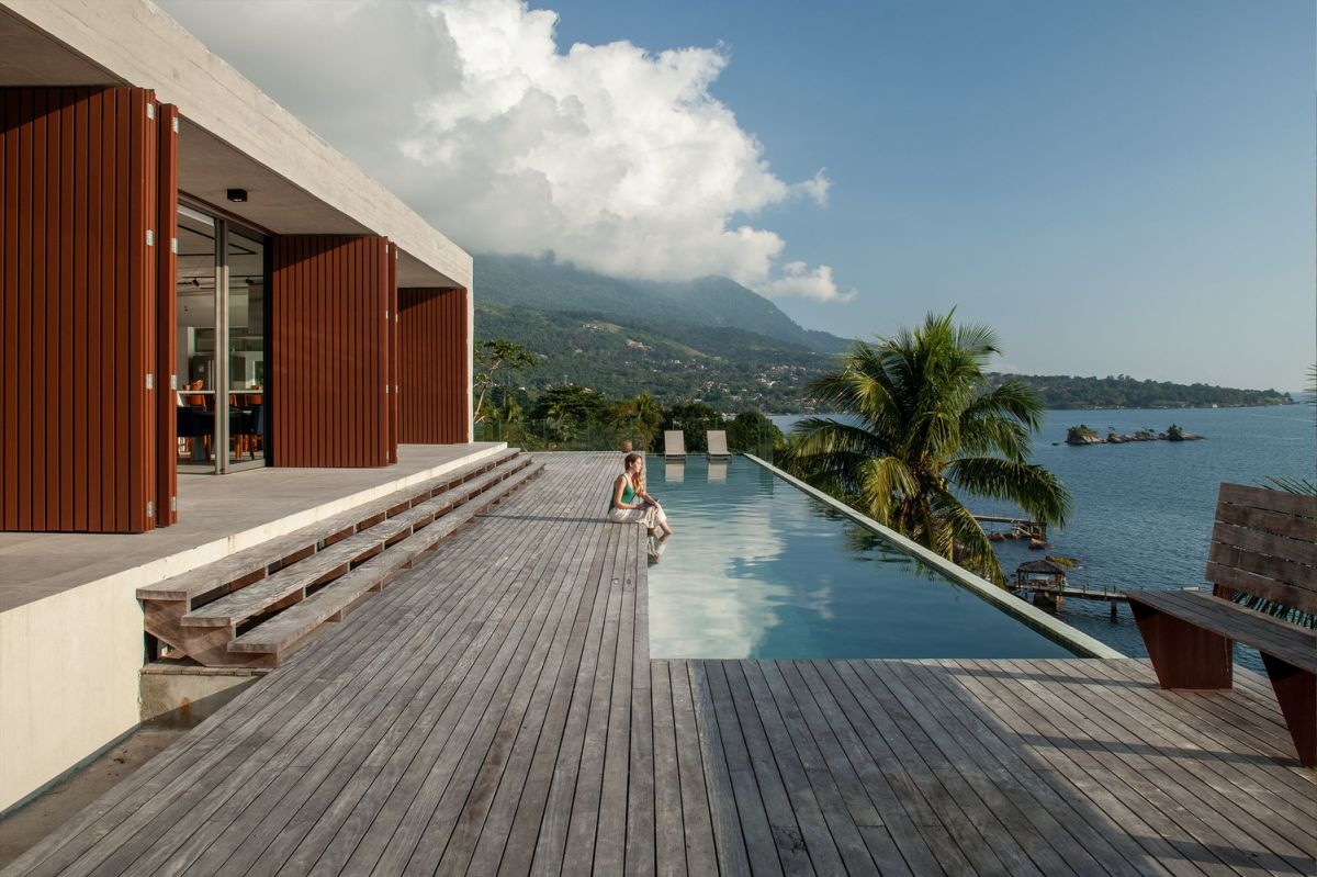 the main volumes opens up towards a wooden deck with an infinity pool