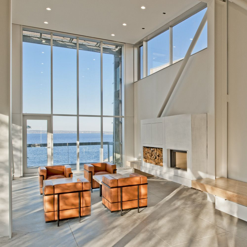 The living room is very bright, with white walls, large windows and very little furniture overall