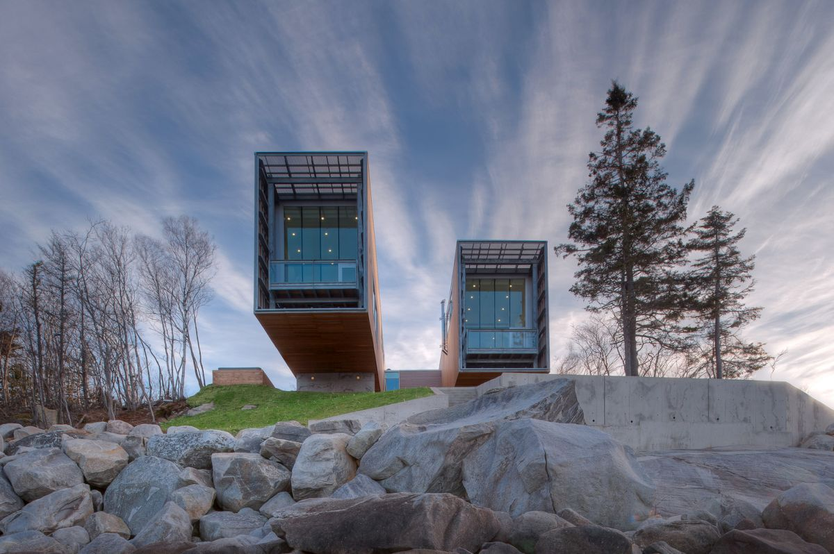 The pavilions have steel frames covered in a wooden skin and end in terraces with glass railings