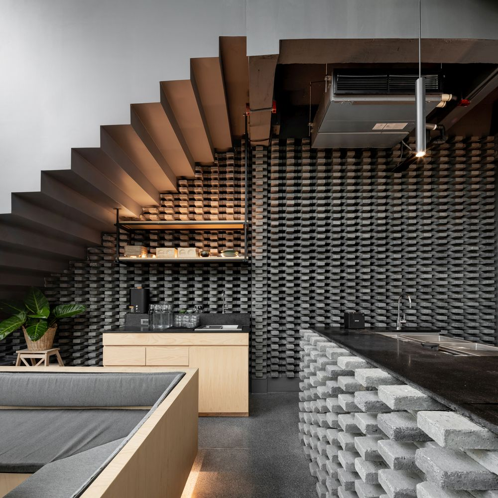 The bar and the wall adjacent to it feature a grey brick pattern that contrasts with the warm wooden surfaces around it