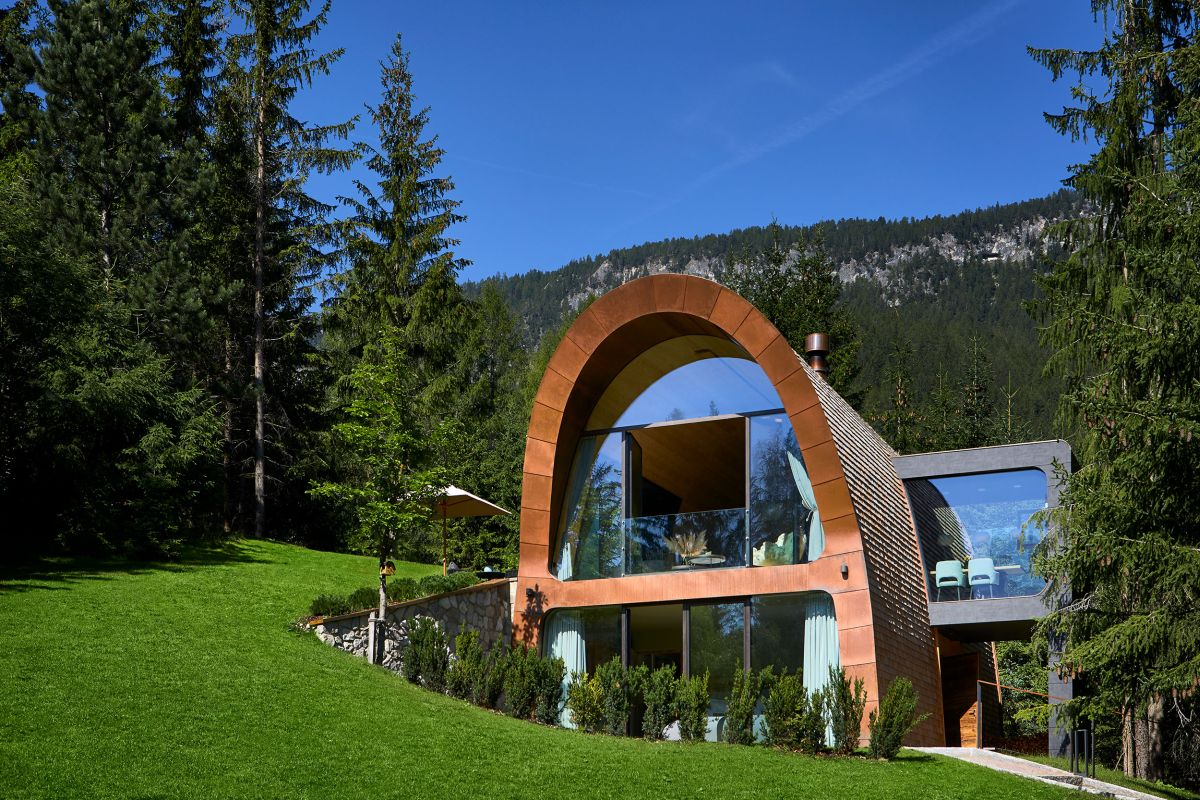 The chalet disappears partially into the hillside, forming a small courtyard around it