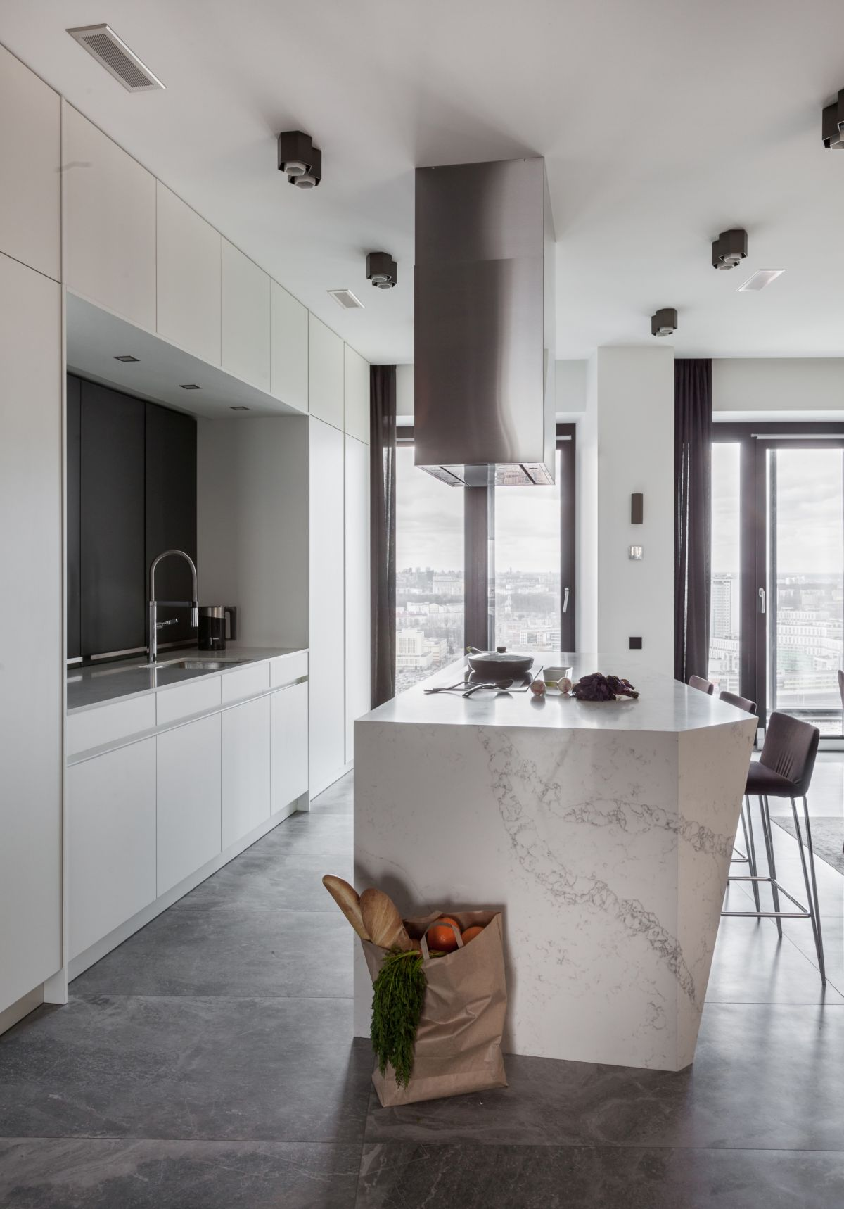 The kitchen is almost entirely white and has a massive and elegant island made from white marble