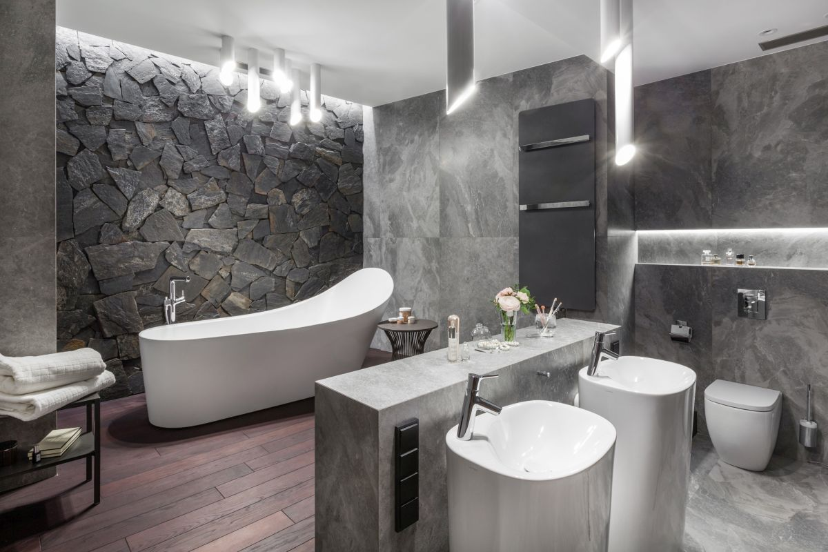 The master bathroom is designed with tones of gray and dark-stained wood for a spa-like vibe